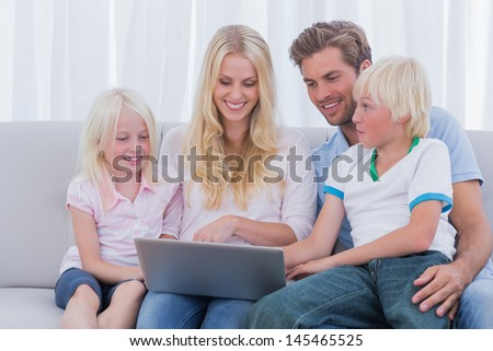 Family using laptop in the living room - stock photo