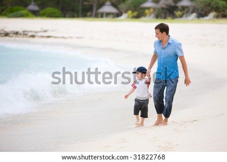 Family vacation. Happy father and son on the beach. - stock photo