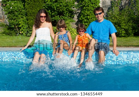 Family vacation, happy parents with two kids having fun and splashing near swimming pool in summer