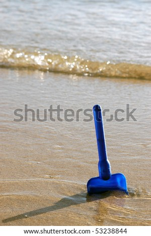 Family vacation image of a child's toy spade in the sand on a beach, with copy space - stock photo