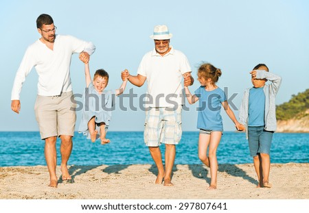 Family vacation on the beach. Group of five. Grandfather and father are carrying a toddler, two seven year young girl and a boy next to them, all holding hands. - stock photo