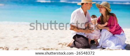 Family vacation. Panoramic photo of young family of three on white sand tropical beach - stock photo