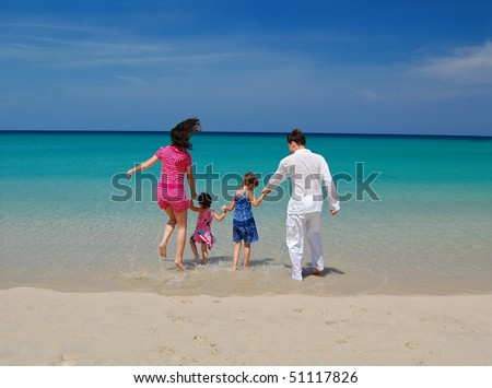Family vacation. Parents with two children on the beach - stock photo