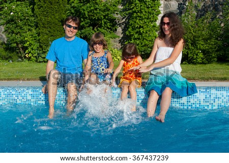 Family vacation, parents with two kids having fun near swimming pool  - stock photo