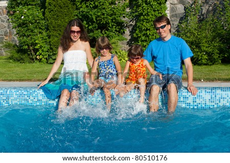 Family vacation. Parents with two kids having fun near swimming pool - stock photo