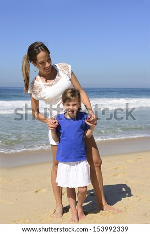 Family vacation: Portrait of mother and daughter on the beach - stock photo