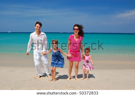 Family vacation. Smiling parents and two children on the tropical beach - stock photo
