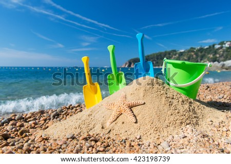 Family vacation with toys in the sand - stock photo