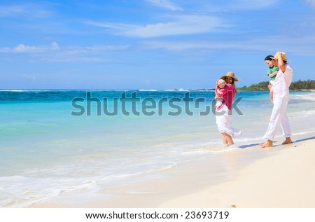 Family vacation. Young family of four on white sand tropical beach - stock photo