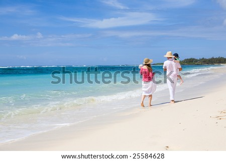 Family vacation. Young family of four walking along white sand tropical beach - stock photo