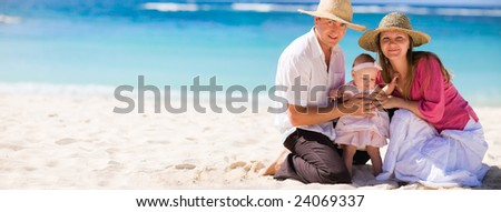 Family vacation. Young family of three on white sand tropical beach - stock photo