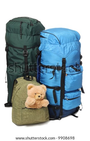 Family vacations. Two big backpacks and children's bag with toy, isolated on white background - stock photo