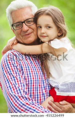 Family values concept. Portrait of stylish and fashionable grandparent with grandchild sitting in his hands. Close up. Outdoor shot - stock photo