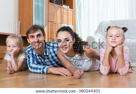 Family values: portrait of smiling spanish  parents with little girls indoors