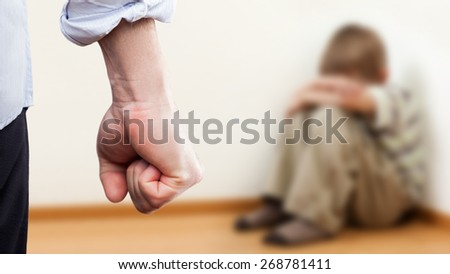 Family violence and aggression concept - furious angry man raised punishment fist over scared or terrified child boy sitting at wall corner - stock photo