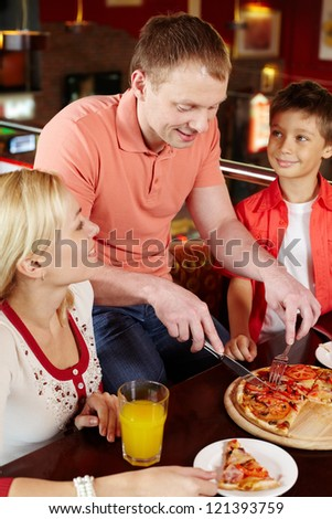 Family waiting for their father to cut an appetizing pizza in pieces - stock photo