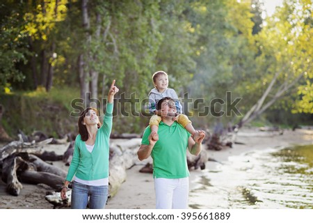 Family walk along the shore. Dad keeps son on shoulders, mother's pointing hand up, everyone looking up.