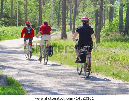 Family walk on bicycles on wood road - stock photo