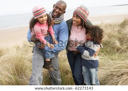 Family Walking Along Dunes On Winter Beach - stock photo