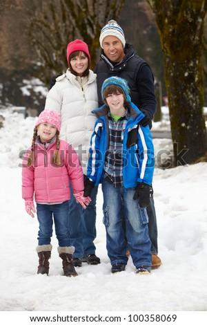 Family Walking Along Snowy Street In Ski Resort - stock photo