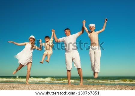 Family walking along the beach while on vacation - stock photo