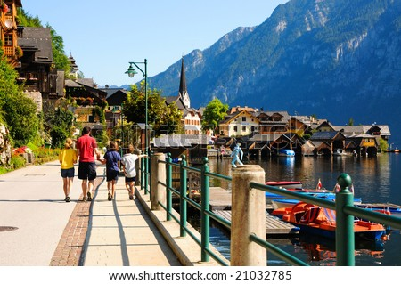 family walking along waterfront, Halldstadt, Austria - stock photo