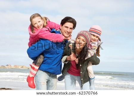 Family Walking Along Winter Beach - stock photo