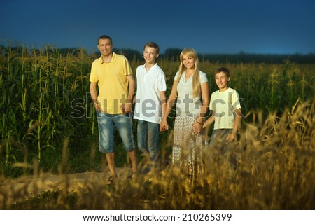 Family walking by road in field at night