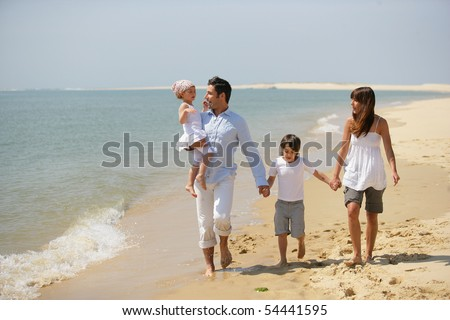 Family walking by the edge of the sea