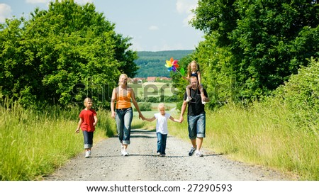 Family walking down a path on a bright summer day, a village in the background - stock photo