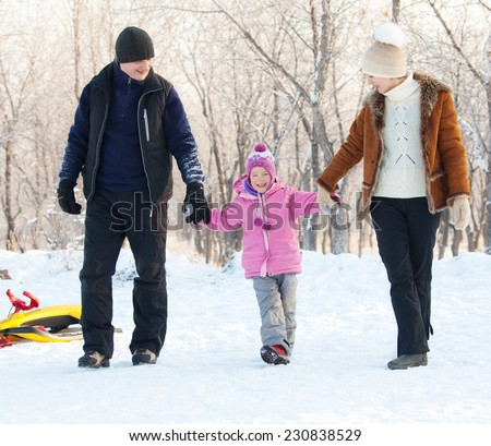 Family walking in a winter park. Parents with child  - stock photo