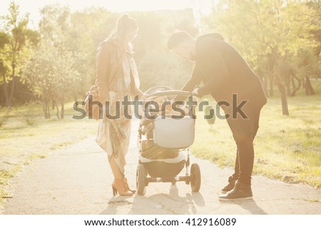 Family walking in park with a child in pram in sunny warm day - stock photo