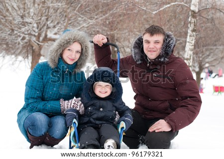 Family walking in the park during the winter snowfall