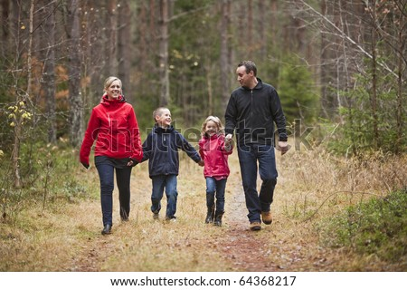 Family walking in the woods - stock photo