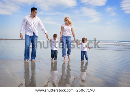 Family walking on a beach, all wearing jeans and white shirts - stock photo
