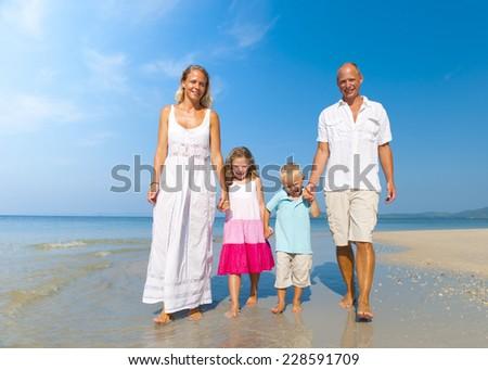 Family walking on beach. - stock photo
