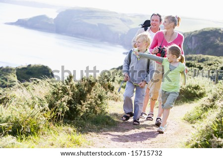 Family walking on cliffside path pointing and smiling - stock photo