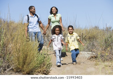 Family walking on path holding hands and smiling - stock photo