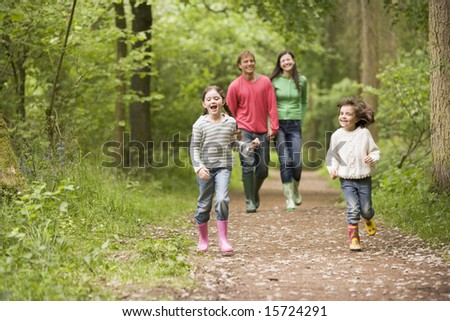 Family walking on path holding hands smiling - stock photo