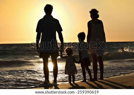 Family walking on the beach in sunset - stock photo
