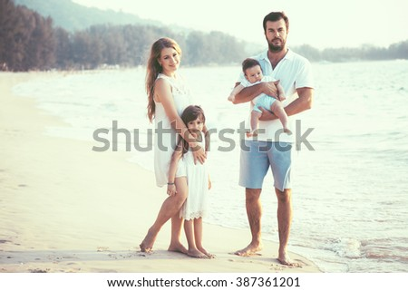 Family walking on the evening beach during sunset. Children with parents.