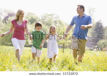 Family walking outdoors holding flower smiling - stock photo