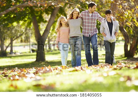 Family Walking Through Autumn Woodland - stock photo