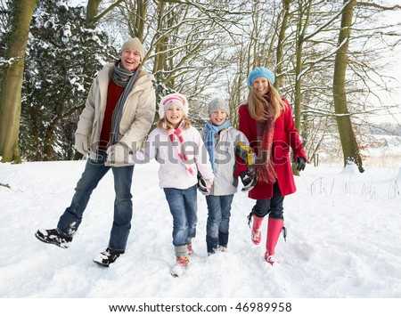 Family Walking Through Snowy Woodland - stock photo
