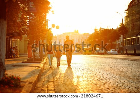 family walking together on the sunset by the road on the cityscape - stock photo