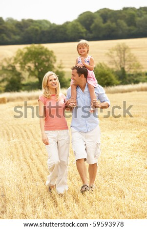 Family Walking Together Through Summer Harvested Field - stock photo