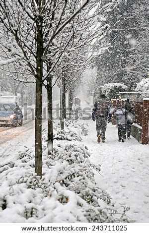 family walks in the city  sidewalk during a winter snowfall - stock photo