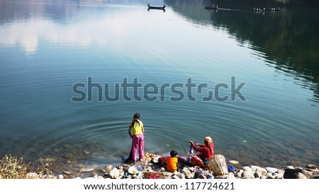 Family washing cloth in the Pokhara lake of reflection of sky and clouds in countryside pokhara, nepal, southern asia developing country, Simply life - stock photo