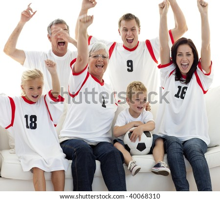 Family watching a football match and celebrating a goal at home - stock photo