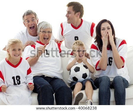 Family watching a football match in television at home - stock photo